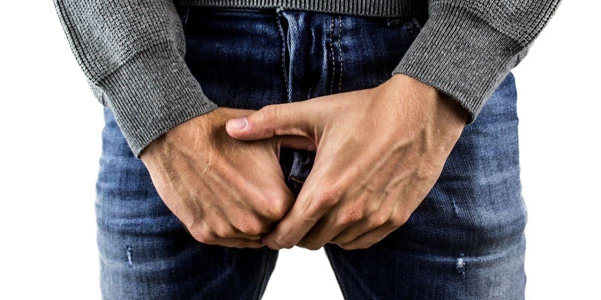 hombre sujetando sus testículos
