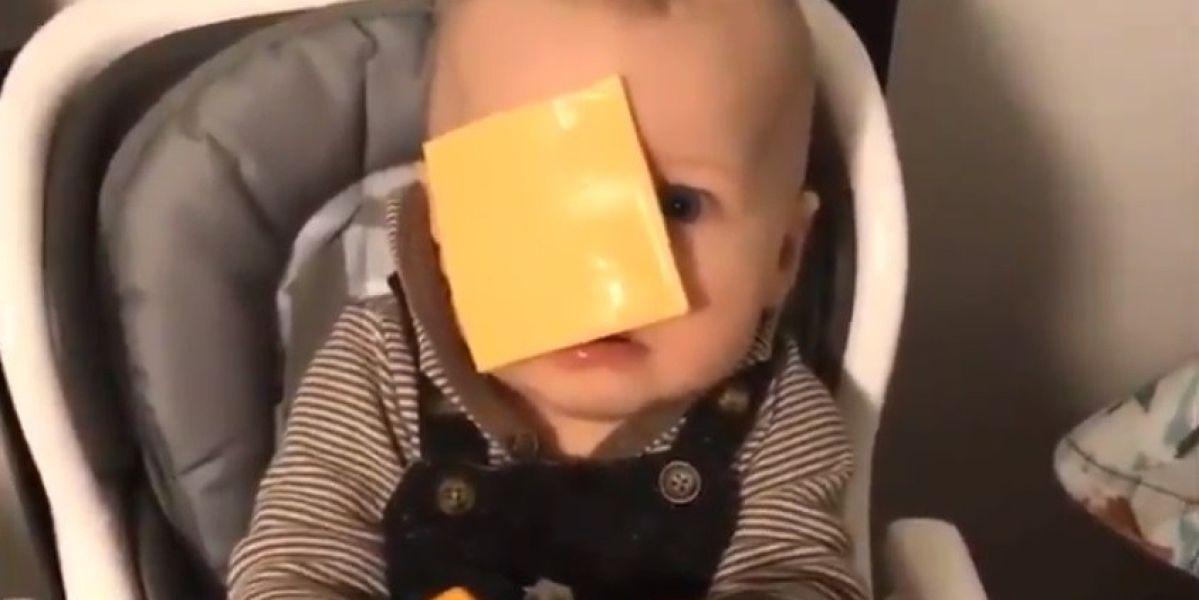 Un bebé con una loncha de queso en la cara.