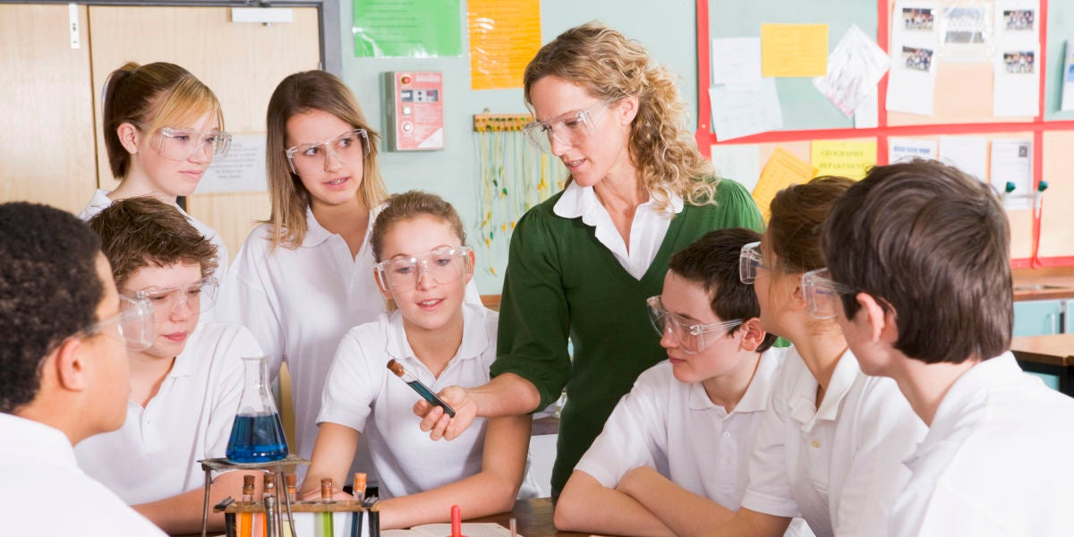 Una profesora y varios alumnos en una clase de química
