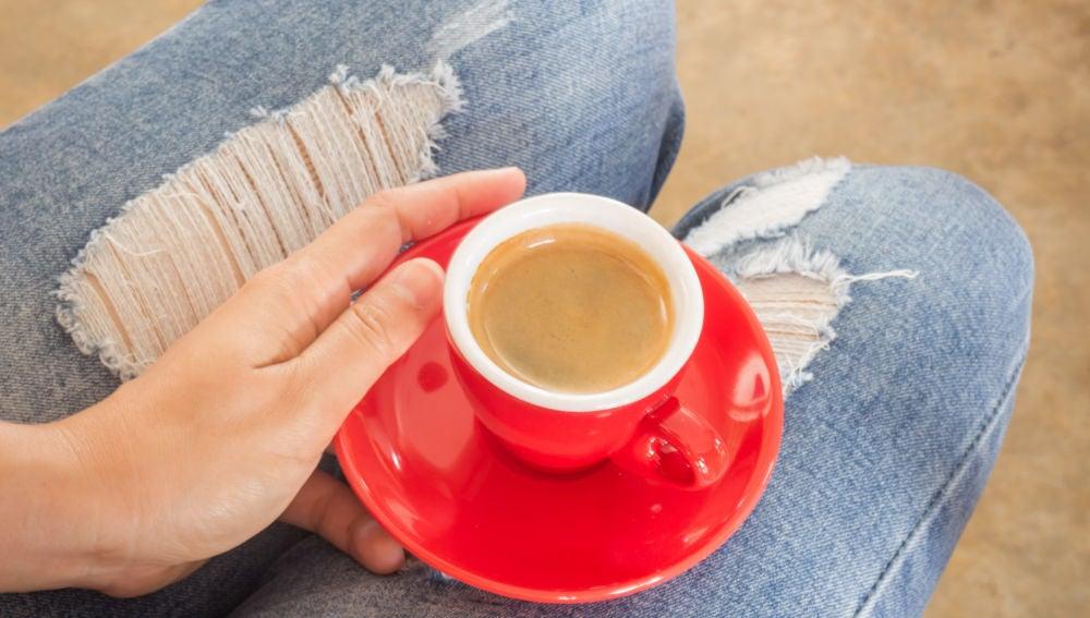 Chica con jeans tomándose un café