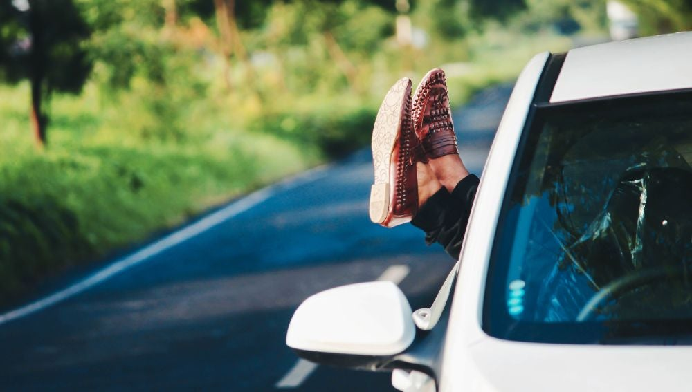Una mujer sacando los pies por la ventanilla del coche
