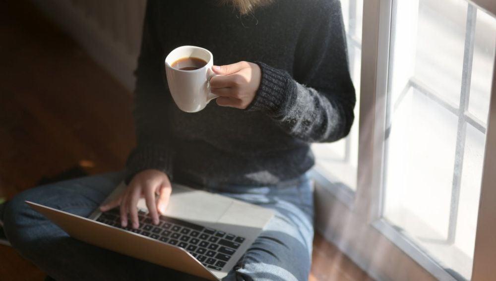 Una mujer bebiendo café y usando el portátil