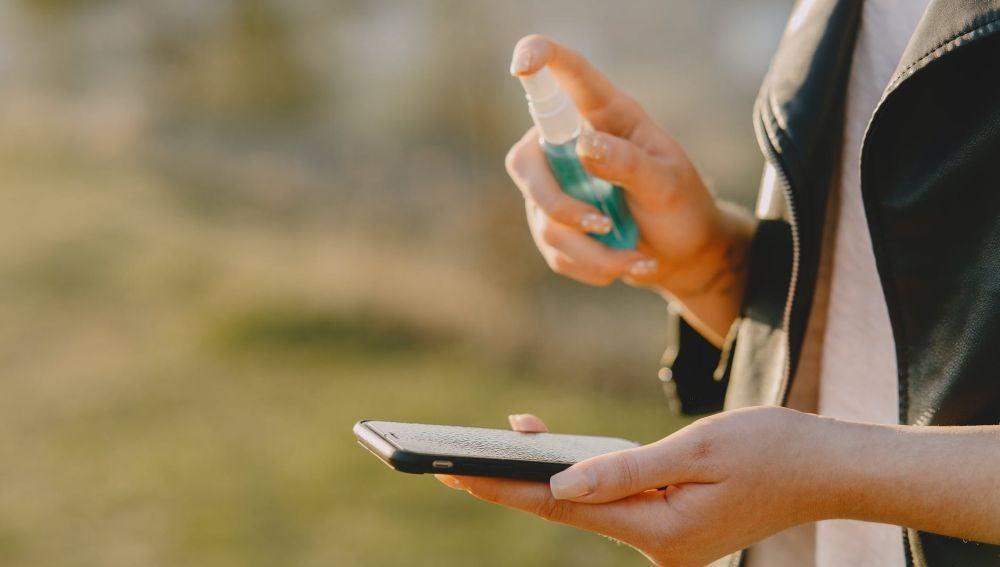 Una mujer desinfectando su teléfono móvil