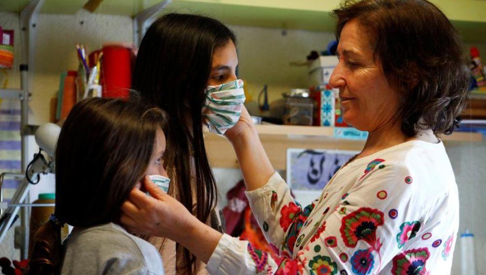 Una mujer prueba mascarillas a dos niñas