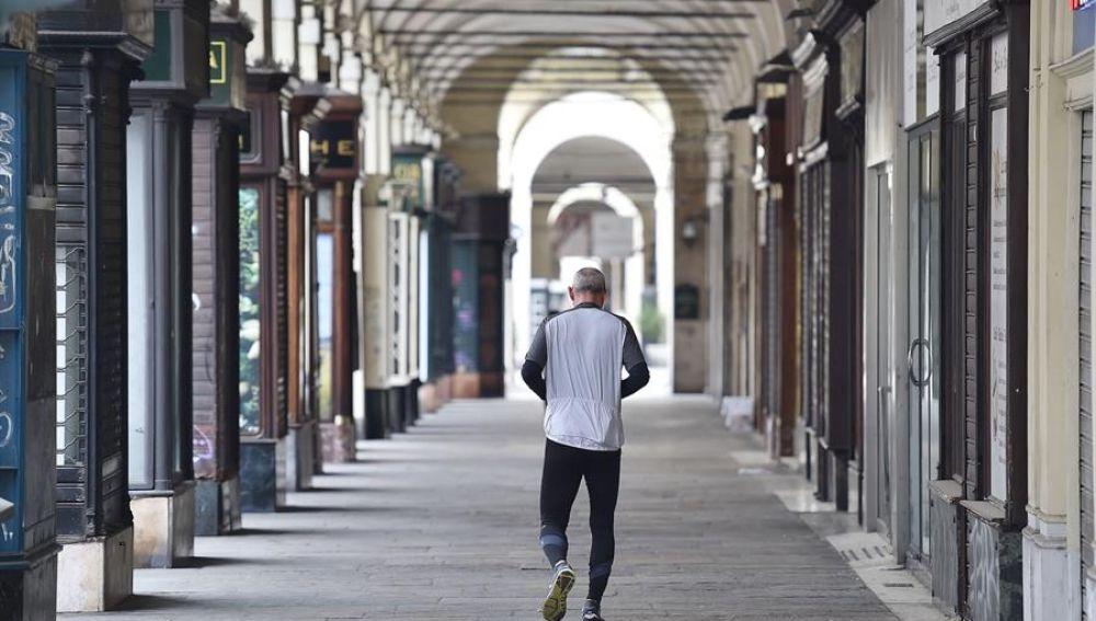 Un hombre camina por una calle vacía de Turín.