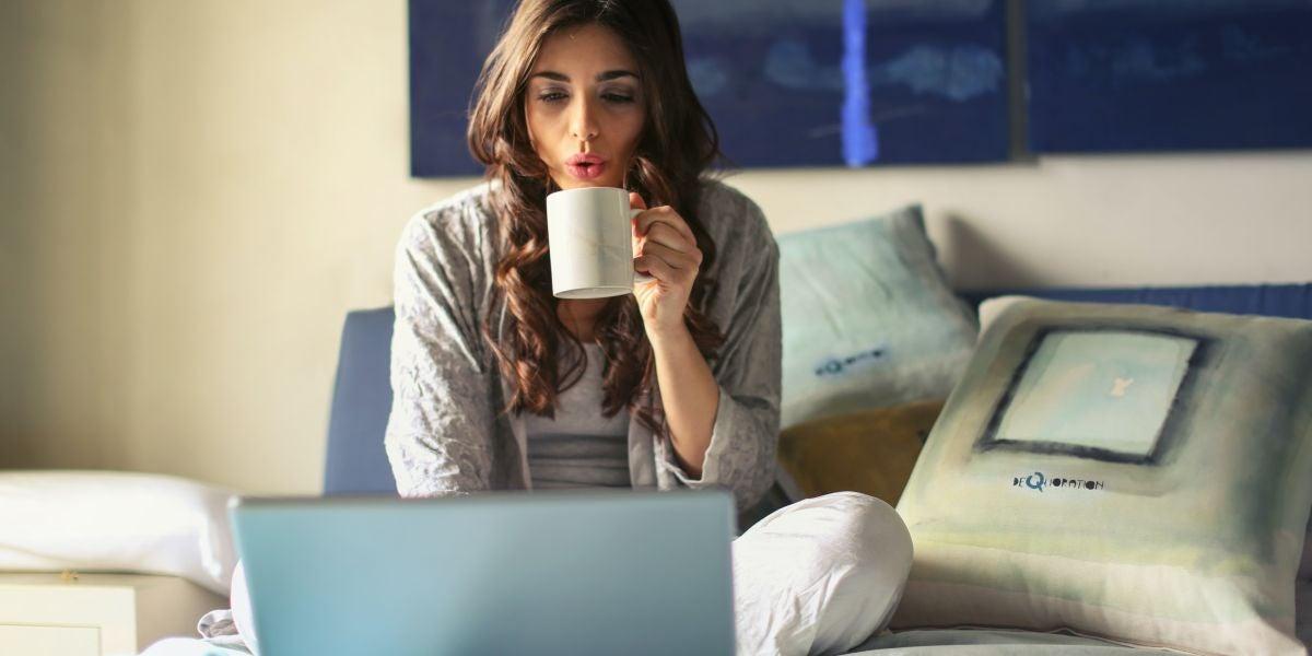 Una chica utilizando su portátil en la cama