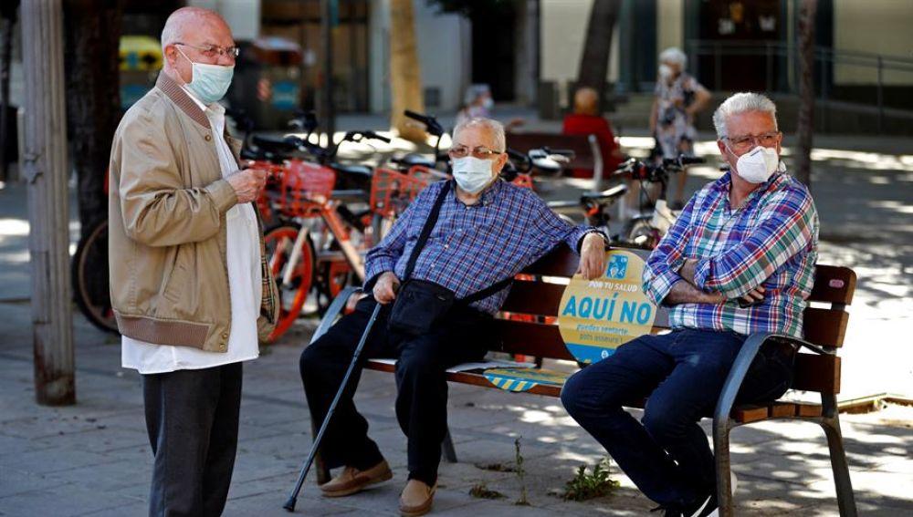 Tres hombres con mascarilla para evitar la propagación del covid-19.