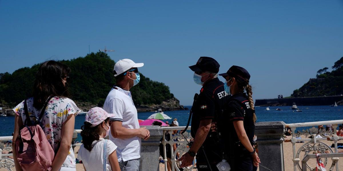 Una familia dialoga con agentes de la Policía en la playa de Ondarreta, en San Sebastián