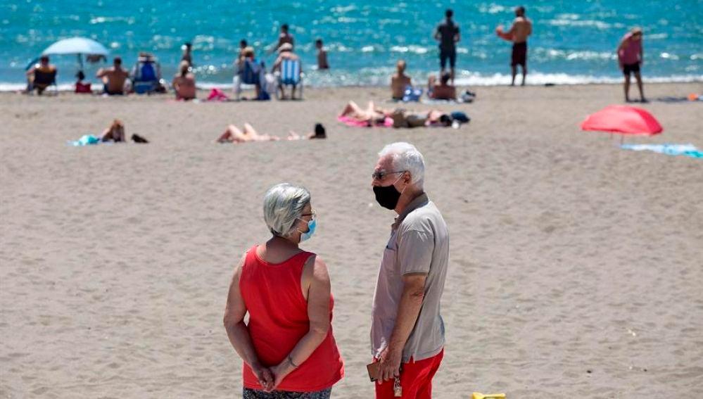 Personas con mascarilla en una playa
