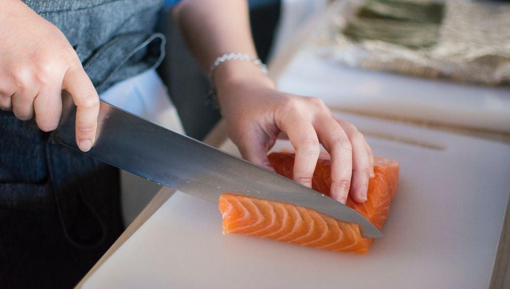 Una persona cortando salmón