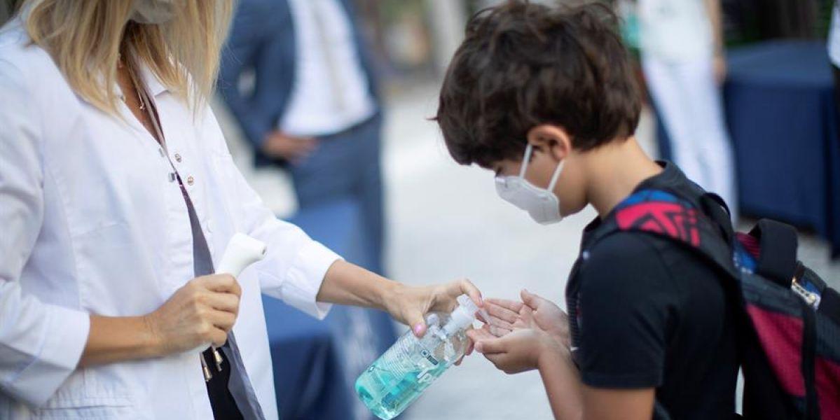 Un niño con mascarilla se lava las manos con gel en un colegio de Barcelona