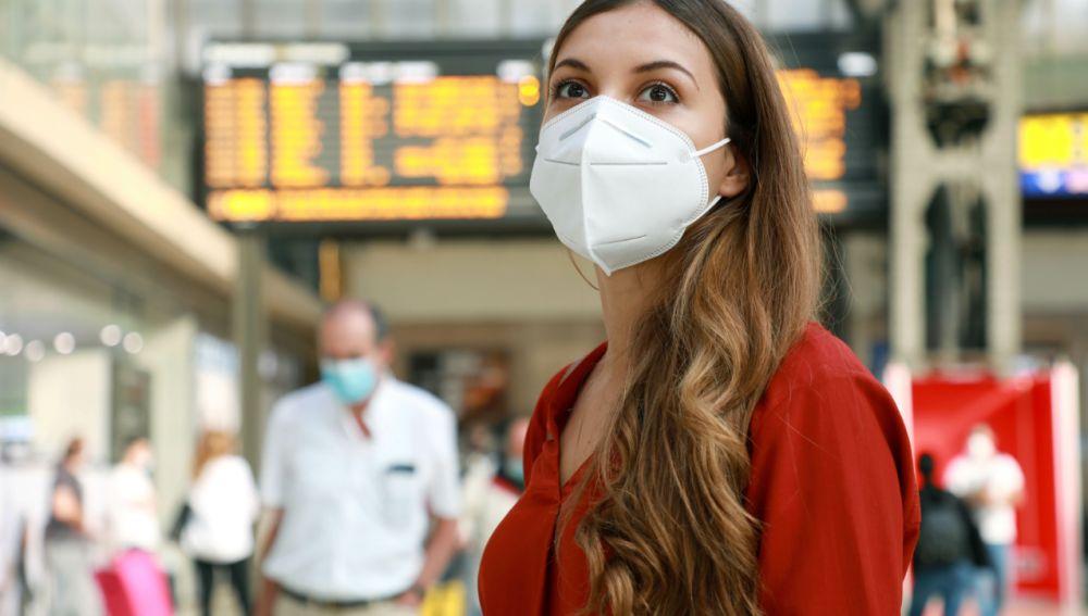 mujer con mascarilla en una estación