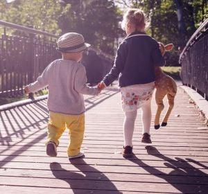 Unos niños caminando de espaldas