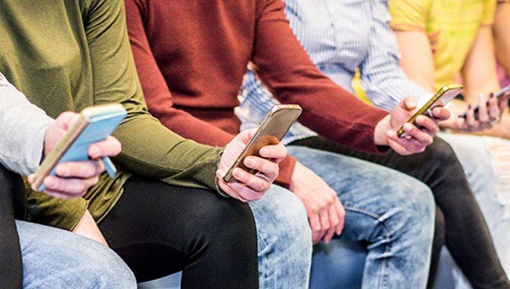 Imagen de archivo de un grupo de jóvenes usando sus teléfonos móviles